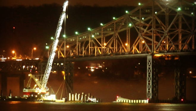 A crane works at night near the Tappan Zee Bridge.