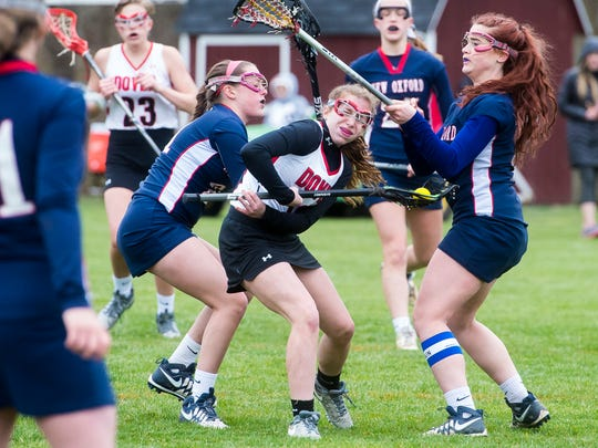 Dover's Paige Lantz squeezes through New Oxford's Brooke-Lynn Grim, left, and Chloe Pevarnick to make a shot on goal during the second half of a girls' lacrosse game on Thursday, March 30, 2017. The Colonials defeated the Eagles 10-7.