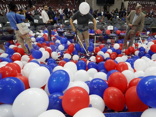 A worker at the Wells Fargo arena pop balloons at the end of the final day of the Democratic National Convention, Friday in Philadelphia.