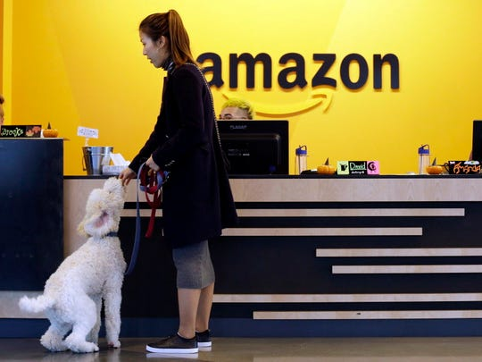 An Amazon employee gives her dog a biscuit on Oct. 11 as the pair head into a company building, where dogs are welcome, in Seattle. Amazon says it received 238 proposals from cities and regions hoping to be the home of the company's second headquarters.