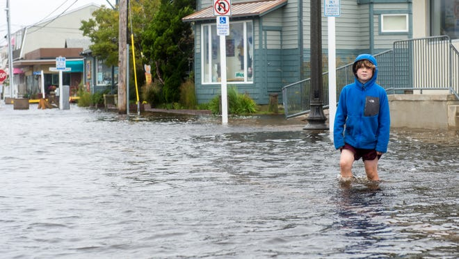 Travis Netting, 9, walks flooded Pennsylvania Ave on Saturday afternoon in Bethany Beach.