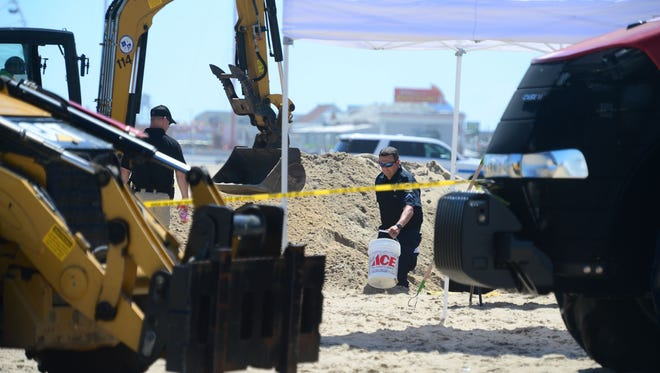 Ocean City Police carry out buckets of sand to be sifted  from a deep hole that was dug around the area where an unidentified body was found this morning around the 2nd Street beach in Ocean City, Md. on Monday, July 31, 2017.