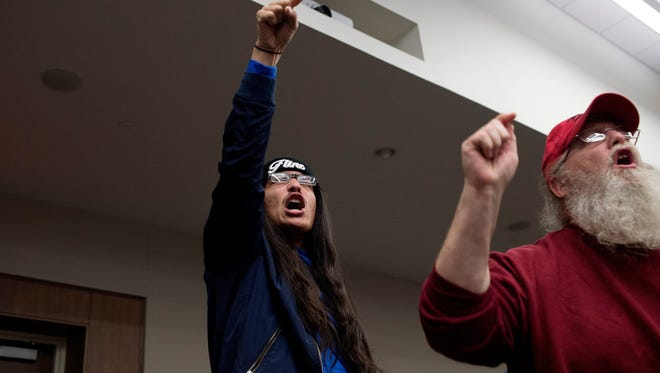 """Abel Delgado, left, and Tony Palladino Jr., both of Flint, chant """"Do your job!"""" during a public hearing on a Nestle Waters North America's proposal to boost the volume of groundwater it pumps for bottling on Wednesday, April 12, 2017 in Big Rapids, Mich.  The company wants to withdraw up to 400 gallons per minute from a well in Osceola County — up from 150 gallons per minute. The request is pending with state regulators.  (Neil Blake/The Grand Rapids Press via AP)"""