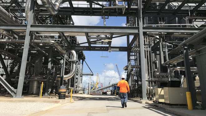 A worker walks on site at Florida Power & Lights Riviera Beach gas-fired power plant. Critics say the utility and the state now rely too much on natural gas, which also contributes to global warming.