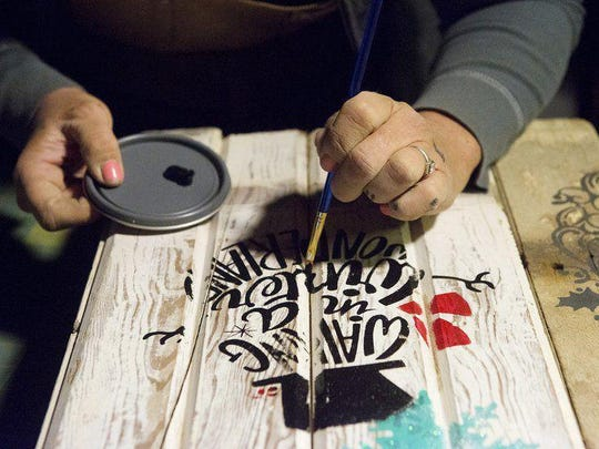 "Angie Gastel McGuire paints a sled Dec. 16 in her Jasper studio. Her ""Junkyard Farmgirl"" business is popular at craft shows. McGuire said she often spends shows running back and forth to her trailer parked outside the venue in order to keep her booth stocked."