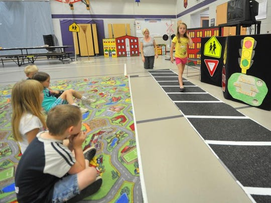 Students learn how to cross a street safely at Safety City, a camp for students who will enter kindergarten, at Grant Elementary School in Wausau. Grant Elementary is one of several elementary schools in the district that could close under a proposed referendum considered by the Wausau School Board.