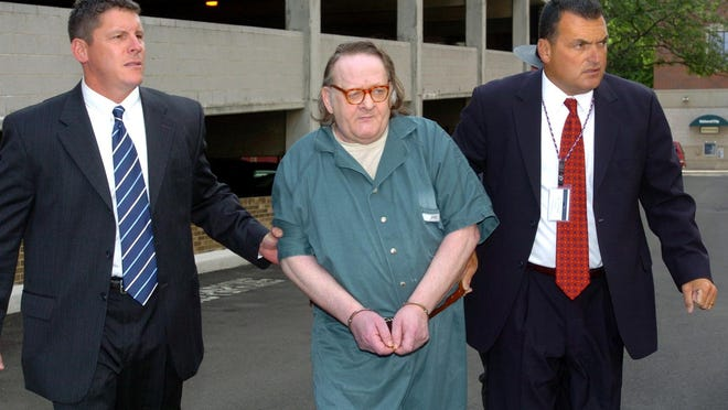 Kenneth E. Barnes, center, is led to the Erie FBI office in July 2007 to be processed before his first federal court appearance in the death of Erie pizza deliveryman Brian Wells in 2003. Escorting him are, at left, Jason Wick, a special agent with the Federal Bureau of Alcohol, Tobacco, Firearms and Explosives, and FBI Special Agent Jerry Clark. Barnes died in federal prison a year ago. He was 65. Both Wick and Clark  are retired from law enforcement and were the lead investigators on the pizza bomber case.