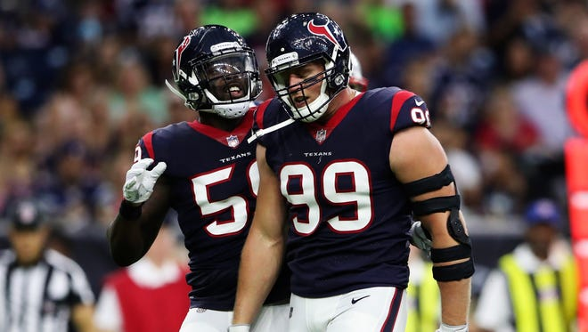 Houston Texans defensive end J.J. Watt (99) celebrates with outside linebacker Whitney Mercilus (59) during the first quarter against the New England Patriots at NRG Stadium.