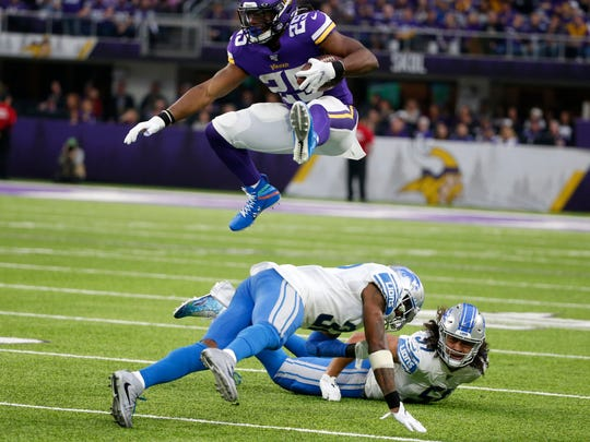 Minnesota Vikings running back Alexander Mattison (25) leaps over Detroit Lions defenders Tavon Wilson and Jahlani Tavai, right, during the first half of an NFL football game, Sunday, Dec. 8, 2019, in Minneapolis. (AP Photo/Bruce Kluckhohn)