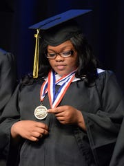 Salutatorian X'Zorriyah Golston looks at her awards while onstage at the Fair Park High School Commencement Exercise.