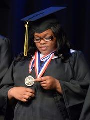 Salutatorian X'Zorriyah Golston looks at her awards