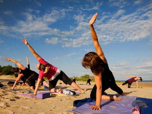 Yoga Instructor Patti Jo Wagner, far right background, leads her Mindful Yoga on the Beach class as students, from foreground, Niccole Matznick of Manitowoc, Brooke Stahl of Two Rivers and Lisa Vieau of Manitowoc reach for the sky at Neshotah Park in Two Rivers on Monday. This 8-week summer yoga class is one of the programs offered by the city of Two Rivers Parks and Recreation Department. Sue Pischke/HTR Media. Photo taken on Monday, July 14, 2014.