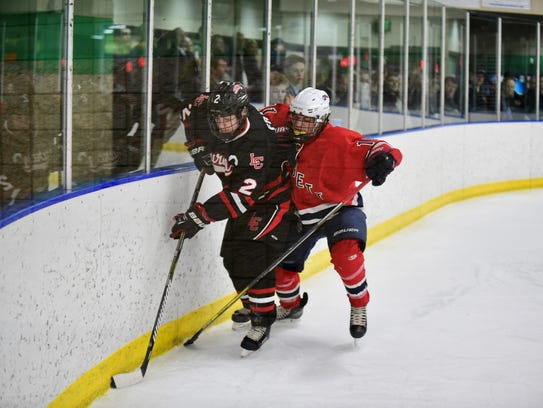 Battling along the boards Wednesday night are Livonia