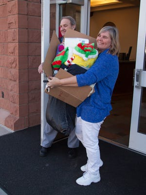 Shelly Reynolds, a teacher at Dixie Sun Elementary, helps distribute donated items to students in need Wednesday, Dec. 16, 2015.