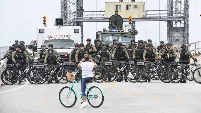 A woman on a bicycle stops to photograph Palm Beach County Sheriff's Office deputies positioned on the West Palm Beach side of the Southern Boulevard bridge, where protesters paused after marching from Dreher Park.