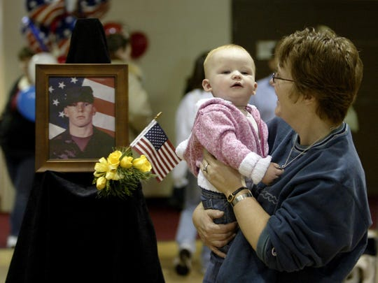 Honoring her father: Ann Byers holds her granddaughter, Haley, after they visited a photo of Haley's father, Sgt. Casey Byers, who was killed while serving in Iraq.