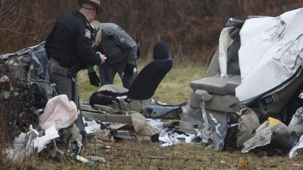 State troopers investigate the wreckage of a vehicle.