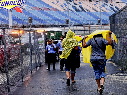Race fans walk through the Fan Zone during a rain shower during qualifying for the NASCAR Camping World Truck Series auto race at Chicagoland Speedway, Friday, Sept. 18, 2015, in Joliet, Ill. (AP Photo/Matt Marton)