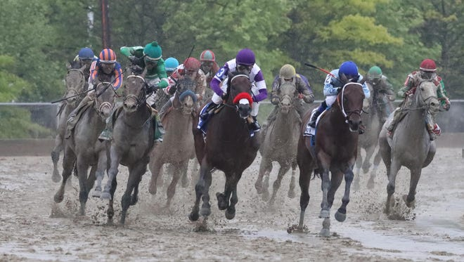 Exaggerator, left, comes off the turn Saturday in the Preakness Stakes.
