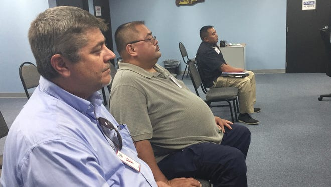 Robert Koss, right, and firefighter John D. Santos, center, listen as the Civil Service Commission voted to initiate an investigation into Santos' whistleblower complaint. Santos alleged there was favoritism in the Guam Fire Department promotions and he was retaliated against for speaking out.