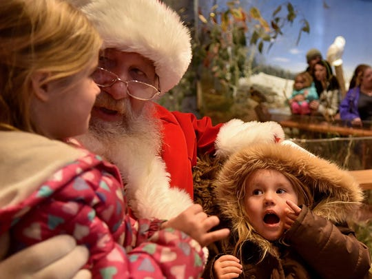 """Autumn Hammes, right, listens to her big sister Jade Wrenn recite her wish list to Santa Claus at the Door County Historical Museum following last year's """"Christmas By the Bay"""" Holiday Parade."""