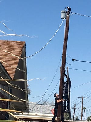 Two men try to rescue a cat trapped March 26, 2018, on a power pole in Phoenix. 911 calls about the cat came from across the USA, bogging down the area's 911 system