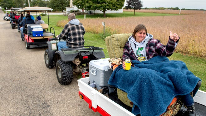 Amy Cunningham of Secor gives the thumbs-up from the comfort of a rocker-recliner to the participants in line behind her as husband Bob tows her with his four-wheeler Saturday, Oct. 3, 2020 during the 13th Annual Secor Golf Cart Poker Run in Secor. Dozens of golf carts and other small, motorized vehicles paraded through the small Woodford County town in a fundraiser for local resident Joshua Mayotte who is fighting cancer.