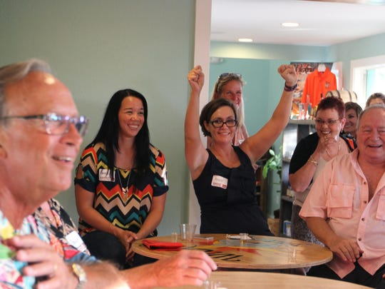 Anne Reed, food and dining writer at The News-Press celebrates as they break out the coconut rum while participating in a rum tasting event at the Wicked Dolphin Distillery in Cape Coral on Wednesday.
