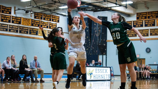 Essex's Rachel Botala (42) leaps past St. Johnsbury's Saleena Porter (00) for a lay up during the girls basketball game between the St. Johnsbury Hilltoppers and the Essex Hornets at Essex High School on Monday night February 12, 2018 in Essex. (BRIAN JENKINS/for the FREE PRESS)