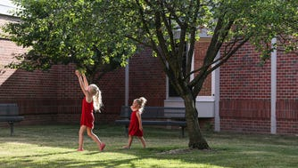 From left, Georgie Ranly, 5, and Beatrice Ranly, 2, picks cherries from a tree at Orchard Park Elementary in Carmel, Ind., while their parents join in a meeting, Monday, June 18, 2018. Parents and community members in the Home Place neighborhood have come together over the last few months to fight the recommendation that Carmel Clay Schools relocate Orchard Park Elementary.