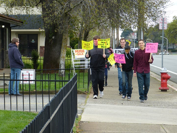 About a dozen people marched from Enterprise High School