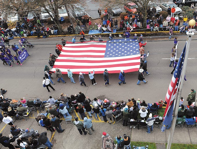 Members of the Willamette Valley Military Masons carry their 20- by 30-foot flag along the Linn County Veterans Day parade route in Albany, Ore.