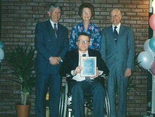 Roger Hartman (center) receives the Alumni Award at