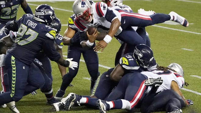 Patriots quarterback Cam Newton is upended by a Seahawk defender as he tries to get into the end zone with three seconds left on the clock. The Pats lost, 35-30.