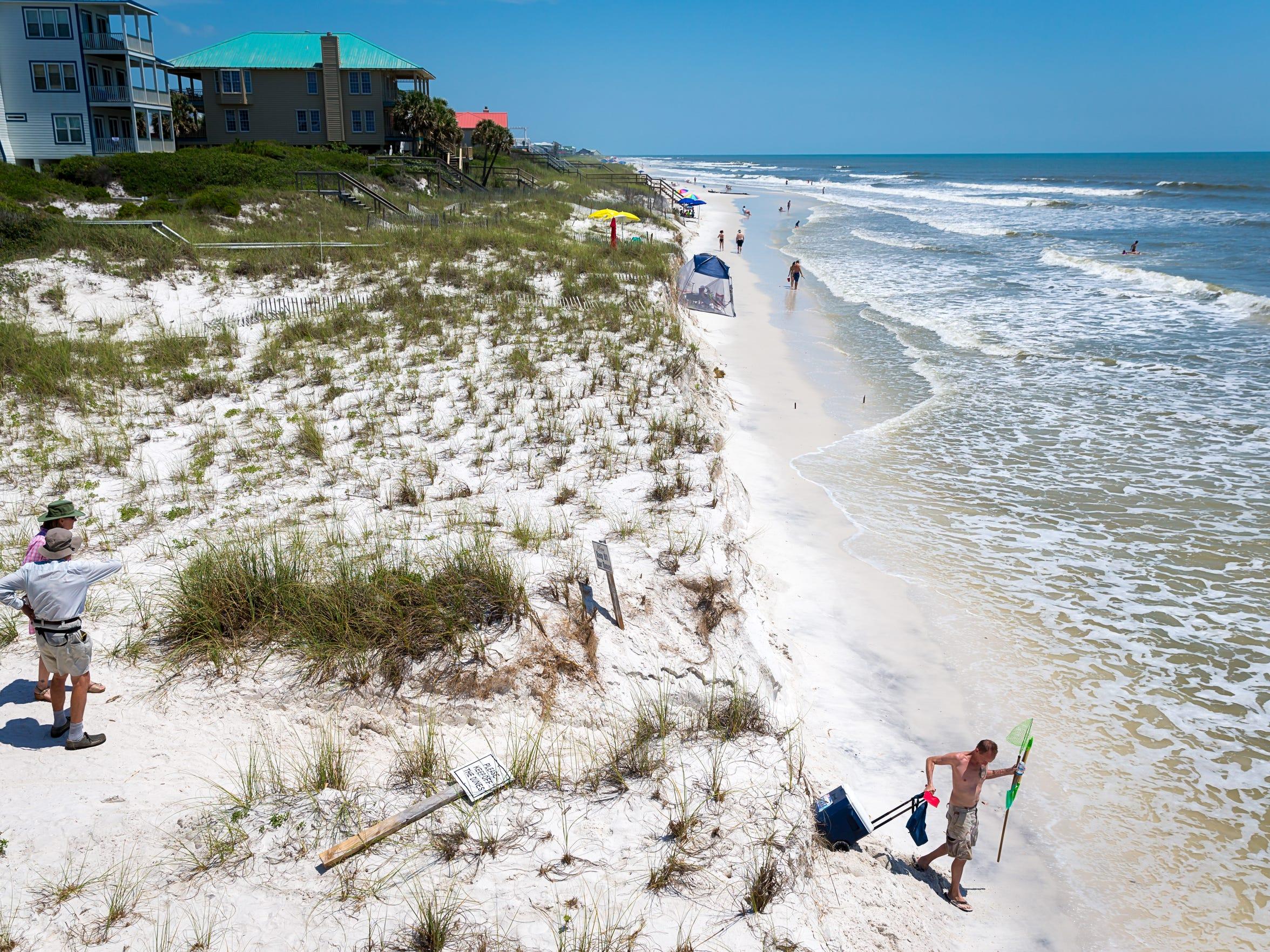 Beachgoers scale an embankment at a public beach access