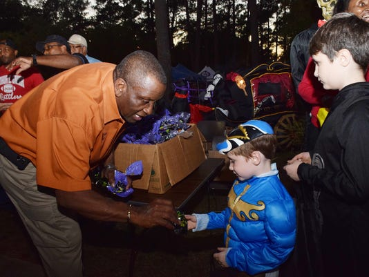 Pineville Mayor Clarence Fields (left) hands out goodies to Bradlee Ryan and his brother Benjamin Ryan at Pineville's 10th annual Fall Family Festival held Thursday, Oct. 29, 2015 at Kees Park. The event included candy and prizes from given by local busine