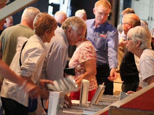"""Audience members get in line for a copy of Dan Egan's new book, """"The Death and Life of the Great Lakes,"""" following his discussion Wednesday at the 2017 Chautauqua Lecture Series."""