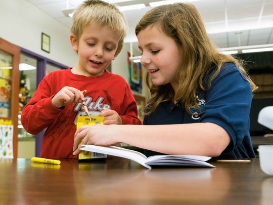 Megan Levering tutors kindergartener Luke Gelman at Maclary Elementary School. Several of the school's fifth-graders, Levering among them, recently volunteered to work with kindergartners to improve their literacy skills.