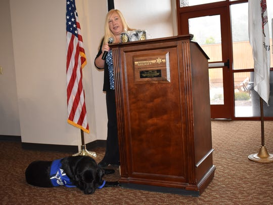 Kim Carroll, senior victim advocate with the Thurston County Prosecutor's Office, and courthouse facility dog Marshal share their experiences with law enforcement at the monthly Mason County Sheriff's Office breakfast, Friday, March 30, at Little Creek Casino Resort in Shelton. Therapy dogs are raised to provide emotional support and comfort to victims in the criminal justice system and are trained from an early age to ignore distractions.