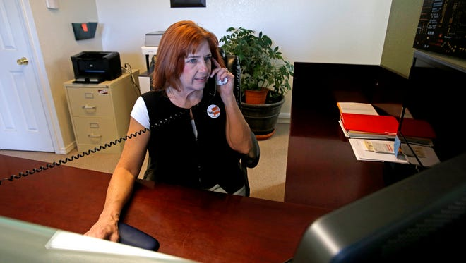 Enrollment counselor Ginger Lewis answers the phone on Friday at the New Mexico Health Insurance Exchange's Farmington Enrollment and Assistance Center.