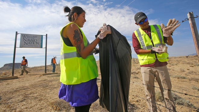 From left, AmeriCorps volunteers Shaneyka Yazzie and Graham Biyaal collect trash on Friday during a volunteer service program hosted by Do Good Diné along U.S. Highway 591 north of Shiprock.