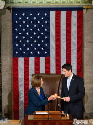 New House Speaker Paul Ryan receives the  gavel from House Democratic leader Nancy Pelosi on Oct. 29, 2015.