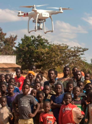 People look on during a drone awareness and safety demonstration on June 22, 2017, under the UNICEF-funded Humanitarian Drone Corridor testing project, in the hard-to-reach rural Chanthunthu Village Health Clinic in Kasungu, Malawi.