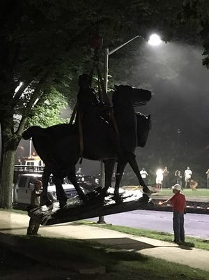 """Workers load statues of Confederate generals Robert E. Lee and Thomas """"Stonewall"""" Jackson on a flatbed truck in the early hours of Aug. 16, 2017 in Baltimore."""