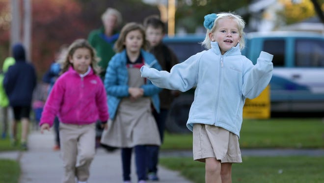 Vivienne Auth, 5, skips along the sidewalk Oct. 7 on her way to St. Margaret Mary Elementary School in Neenah during International Walk to School Day.