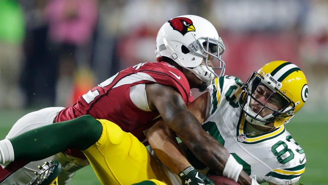Packers receiver Jeff Janis takes a big hit from the Cardinals defender Tony Jefferson.