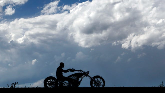 A storm cloud builds behind a biker in the area for the annual motorcycle rally on Fort Meade Way east of Sturgis, S.D.