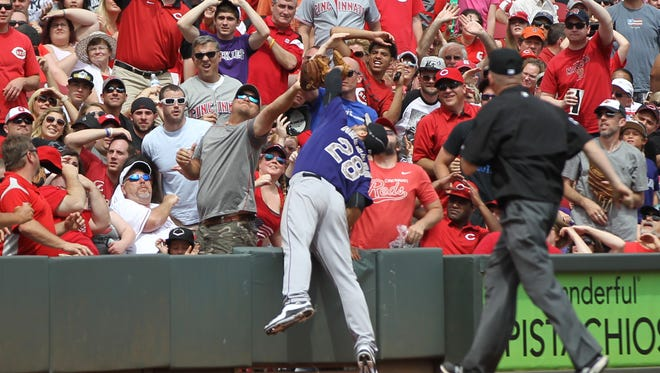 Rockies third baseman Nolan Arenado dives into the stands for a ball off the bat of Zack Cozart for an out in the eighth inning.