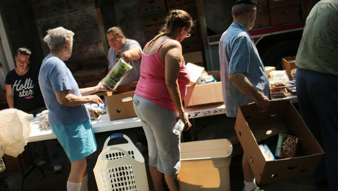 People attend a food distribution by the Food Bank of the Southern Tier Mobile Food Pantry on June 20, 2012 in Oswego, New York.