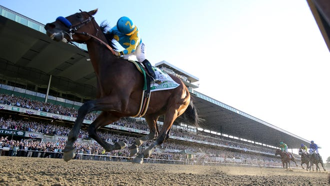 Victor Espinoza celebrates aboard American Pharoah after winning the Belmont Stakes and the Triple Crown.